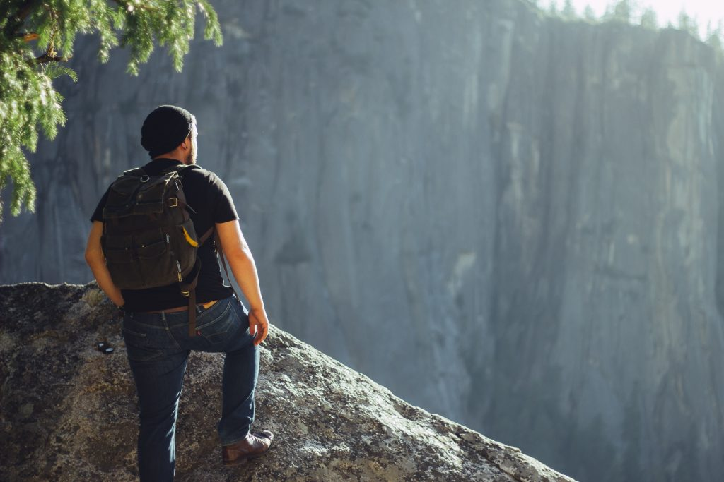 Person looking from top hill view best travel job
